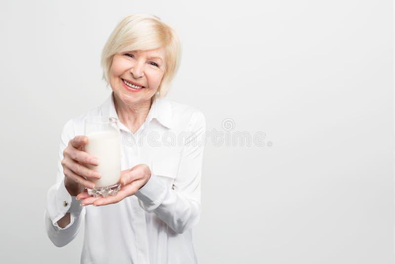 Den härliga mogna kvinnan rymmer en kopp av mjölkar och att le Det goda för ` s som dricker det varje dag Stor vana Isolerat på arkivbild