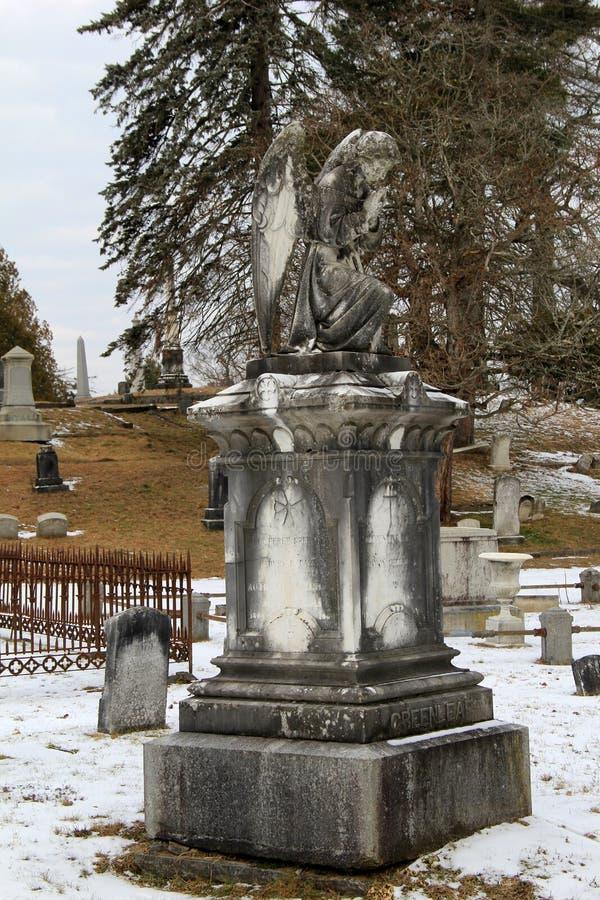 Den härliga monumentet av ängeln och andra gravstenar i vinter snöar, den Greenridge kyrkogården, Saratoga Springs, NY, 2016 royaltyfri fotografi