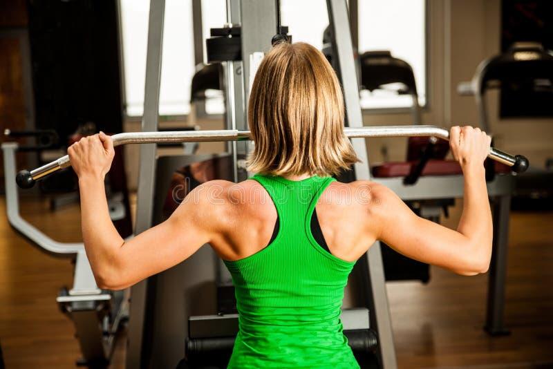 Den härliga muskulösa passformkvinnan som övar byggnad, tränga sig in i fitn arkivfoton