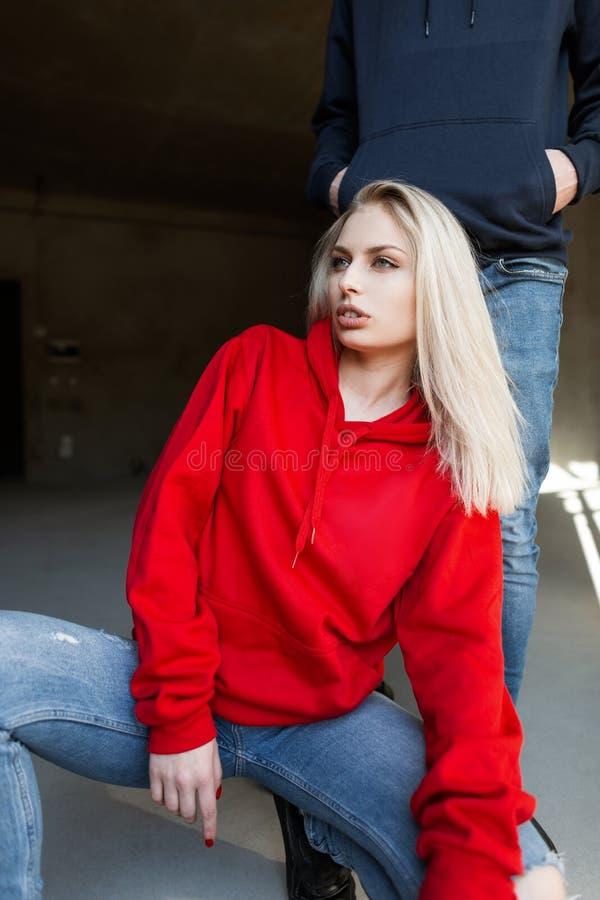 Den härliga nätta unga kvinnliga blondinen i en trendig röd tröja i jeans sitter nära en stilfull ung man i studion arkivbild