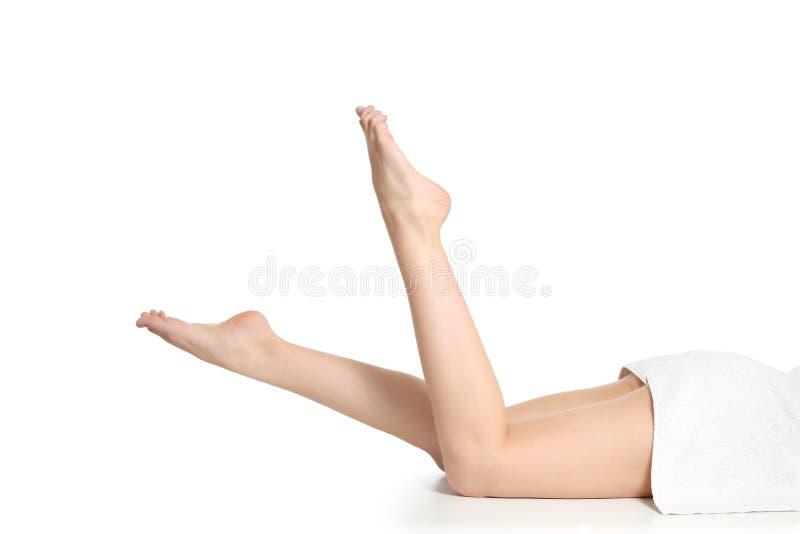 Den härliga nakna kvinnan lägger benen på ryggen i en brunnsort med en handduk royaltyfria foton