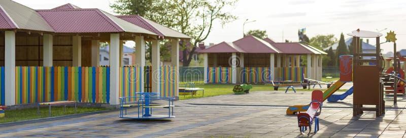 Den härliga nya moderna lekplatsen i dagis med mjuk trottoar, ljusa nya mångfärgade alkov, svänger, glidbanor, bänkar, roun royaltyfri fotografi