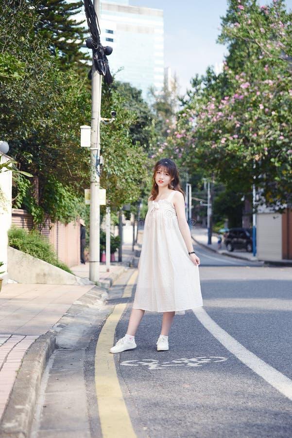 Den härliga och älskvärda asiatiska flickan visar att hennes ungdom i parkerar fotografering för bildbyråer