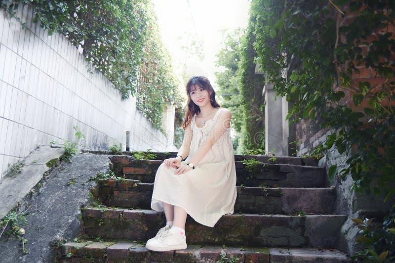 Den härliga och älskvärda asiatiska flickan visar att hennes ungdom i parkerar arkivbild