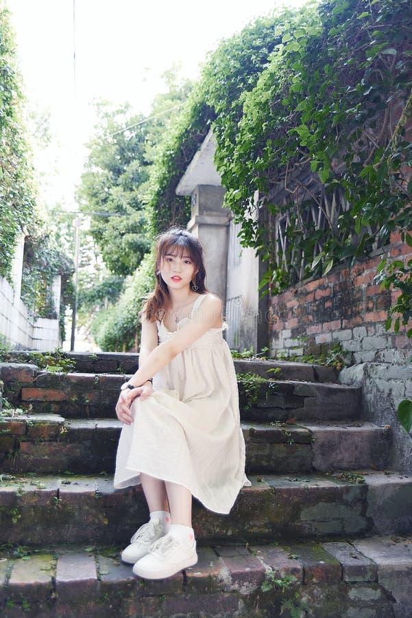 Den härliga och älskvärda asiatiska flickan visar att hennes ungdom i parkerar royaltyfri foto
