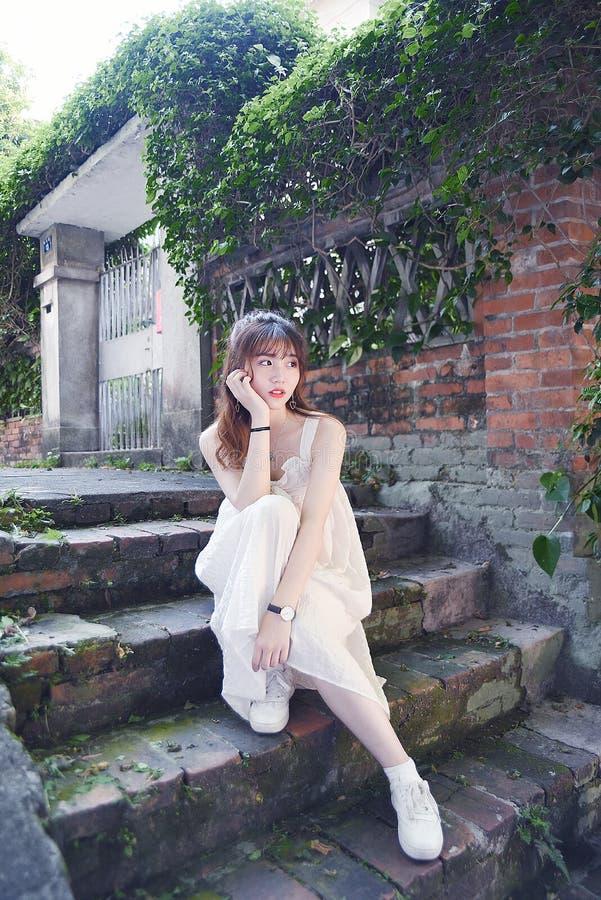 Den härliga och älskvärda asiatiska flickan visar att hennes ungdom i parkerar royaltyfria foton