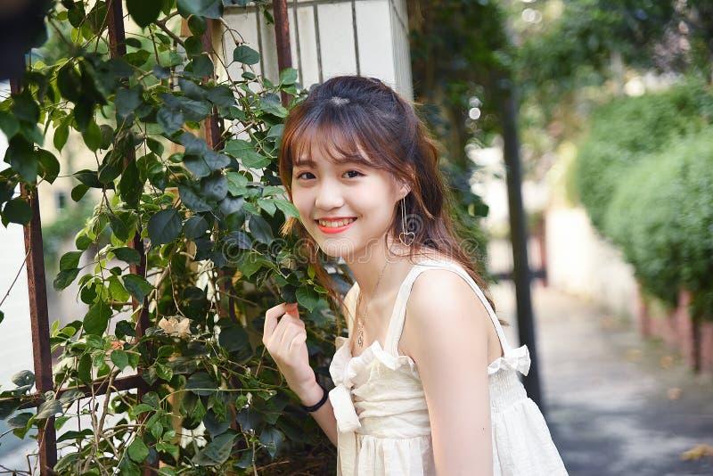 Den härliga och älskvärda asiatiska flickan visar att hennes ungdom i parkerar royaltyfri bild