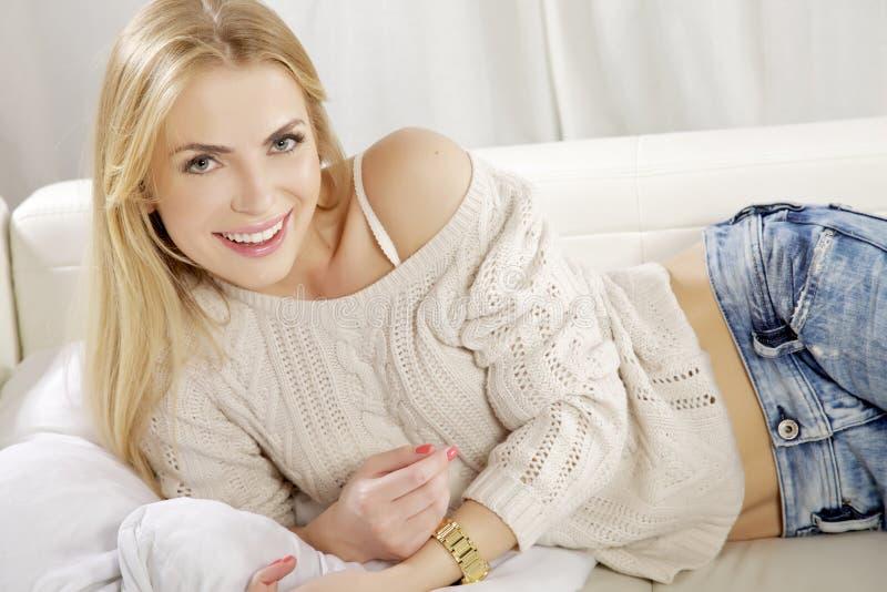 Den härliga och attraktiva blonda kvinnan som poserar i jeans, klär royaltyfria bilder