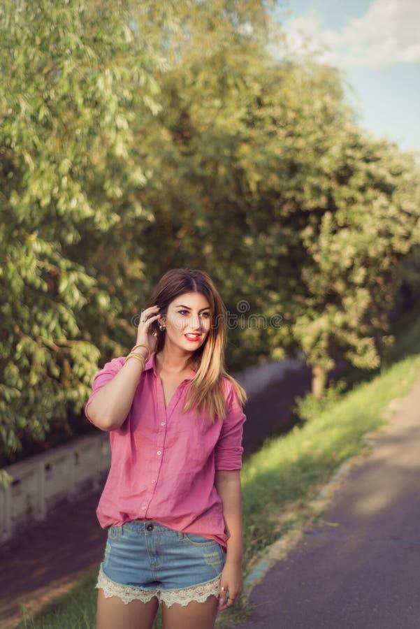 Den härliga och attraktiva kvinnan som åt sidan flyttar henne henne, bärande sexig tillfällig grov bomullstvill, kortsluter fotografering för bildbyråer