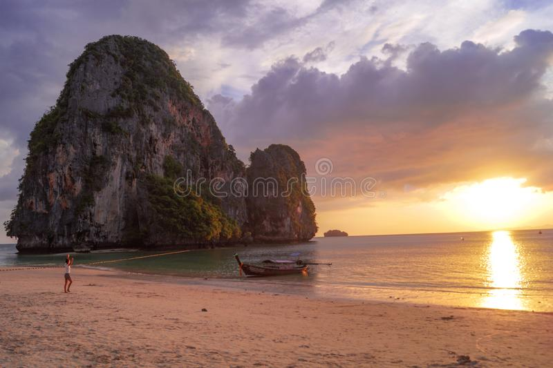 Den härliga och färgrika solnedgången på stranden med vaggar, folk och ett fartyg i Thailand fotografering för bildbyråer