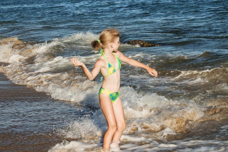 Den härliga och lyckliga flickan i en grön baddräkt kastar en kiselsten i havet, strandbegrepp royaltyfri fotografi