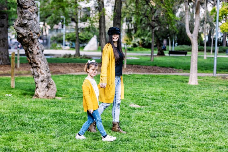 Den h?rliga och lyckliga unga modern som g?r med hennes dotter, b?de som ler och ser in i kameran, parkerar i bakgrund arkivfoton