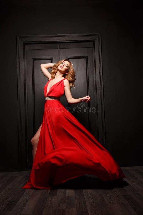 Den härliga och passionerade kvinnan i den röda aftonen som fladdrar klänningen, är tillfångatagandet i flyttning, trädörren är p arkivfoto
