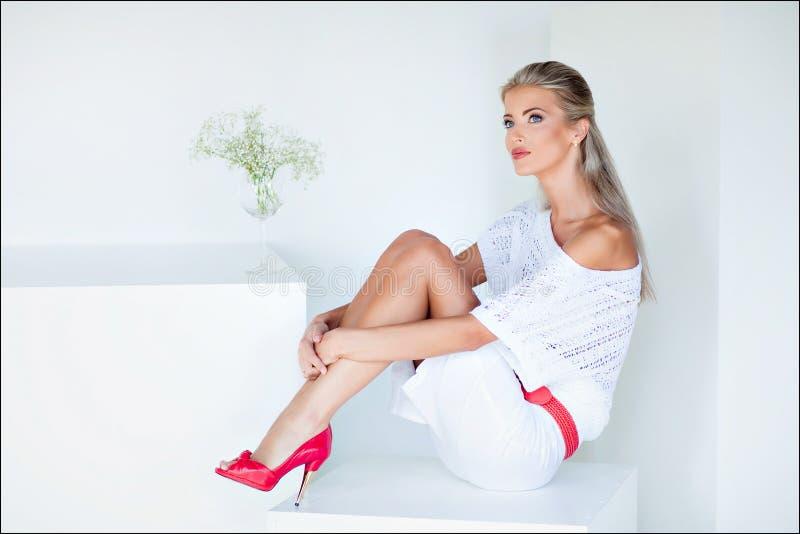 Den härliga och sinnliga blonda flickan i en vit klänning sitter på royaltyfri bild