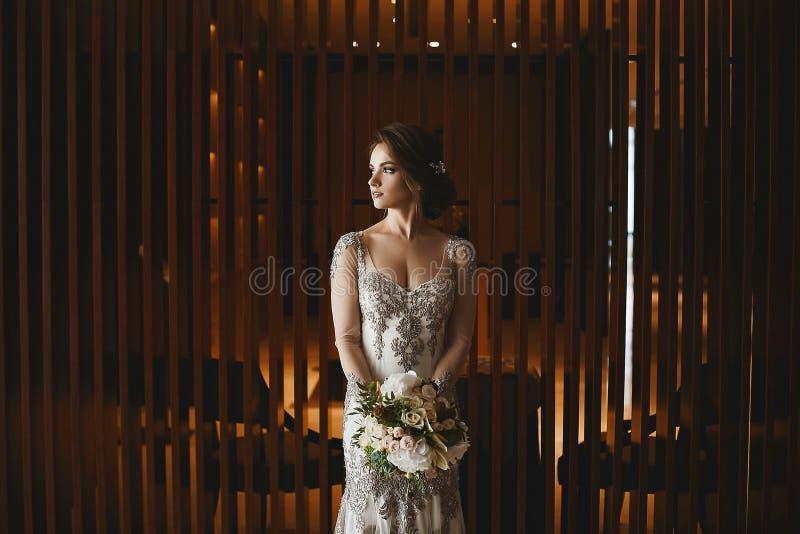 Den härliga och sinnliga brunettmodellflickan med den ljusa makeup- och bröllopfrisyren, i trendig vit snör åt klänningen med buk arkivbilder