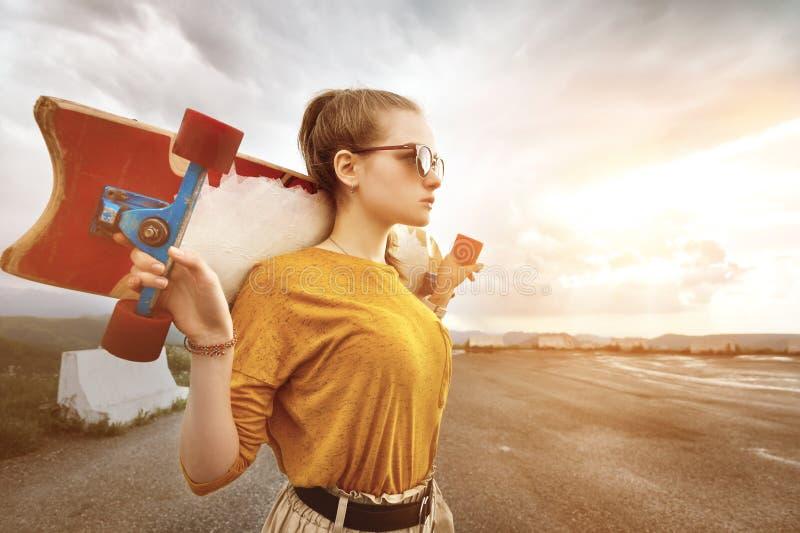 Den härliga och trendiga unga kvinnan i solglasögon och med en tatuering poserar med en skateboard eller en longboard mot arkivbilder