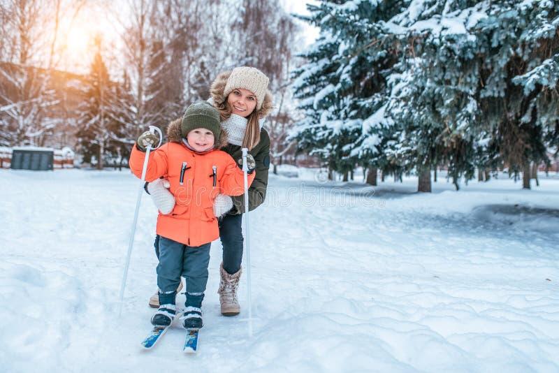 Den härliga och unga modern undervisar för att skida, pysen 3-5 gamla år, son i vinterkläder I vinter i skogen på royaltyfri fotografi