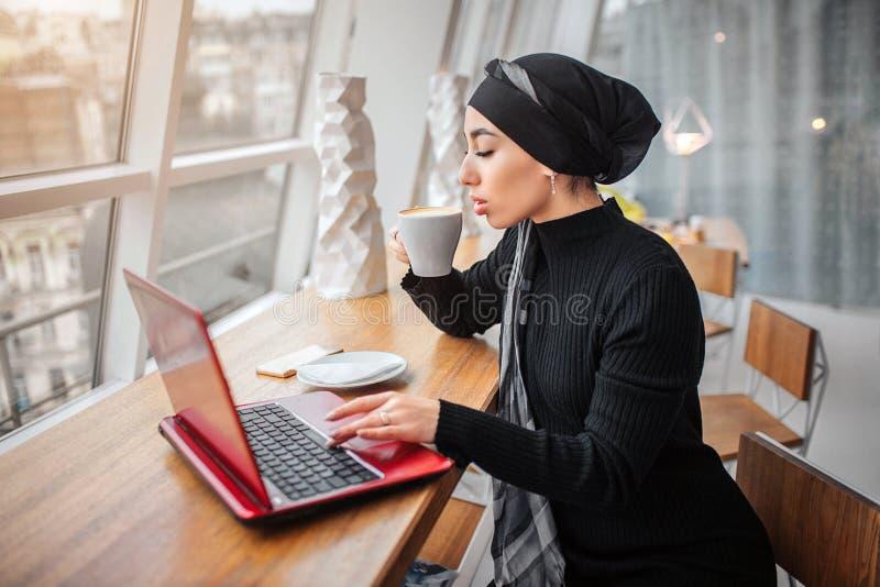 Den härliga och välklädda unga arabiska kvinnan dricker kaffe och arbeten på bärbara datorn Hon sitter på tabellinsidan Den är so fotografering för bildbyråer