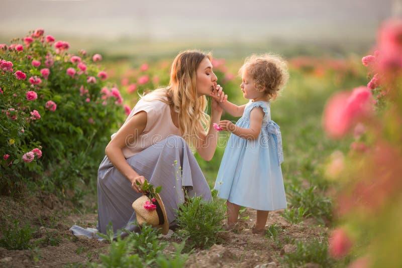 Den härliga parbarnflickan med modern går i vårträdgården med blommor för rosa färgblomningrosor, solnedgångtid royaltyfria bilder