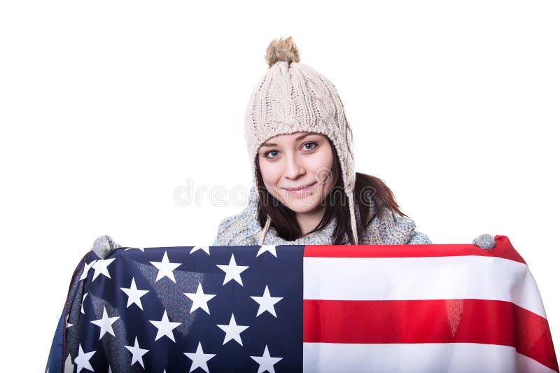 Den härliga patriotiska livliga unga kvinnan med amerikanska flaggan rymde i hennes utsträckta händer som framme står av fotografering för bildbyråer