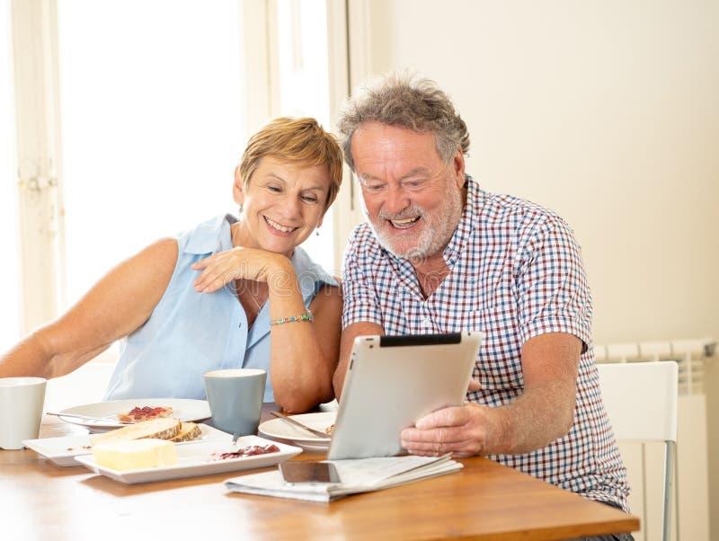Den härliga pensionären avgick gamla par genom att använda den digitala minnestavlan med glädje, medan ha frukosten hemma royaltyfria foton