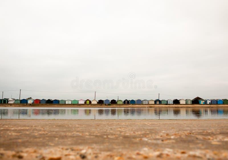 Den härliga platsen av stranden förlägga i barack med reflexioner i vatten framme royaltyfri bild