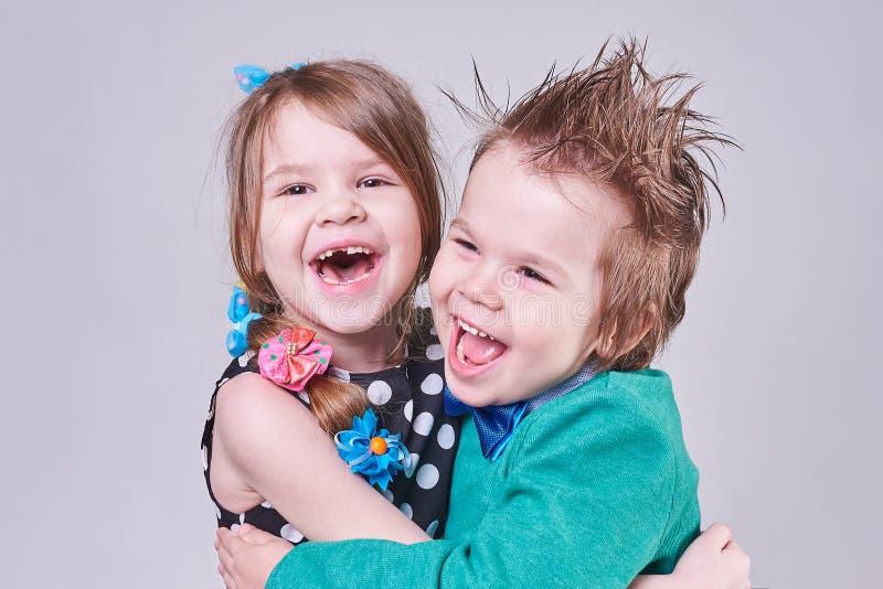 Den härliga pysen och flickan, har roligt skrika och att krama royaltyfri bild