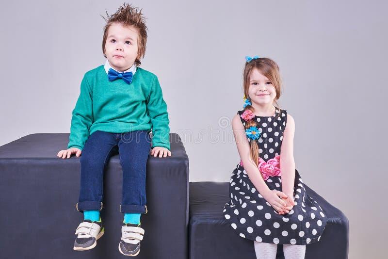 Den härliga pysen och flickan sitter på svarta kuber royaltyfria foton