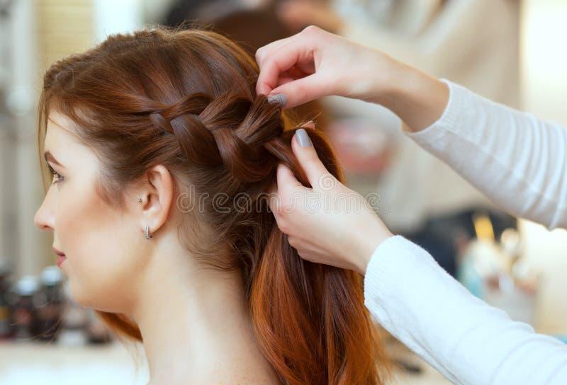 Den härliga rödhåriga flickan med långt hår, frisör väver en fransk flätad tråd, i en skönhetsalong arkivfoto