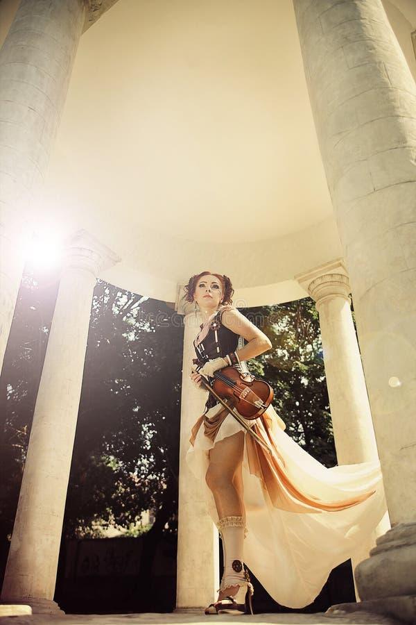 Den härliga redhairkvinnan vaggar in på styleclothes med kroppkonst honom fotografering för bildbyråer