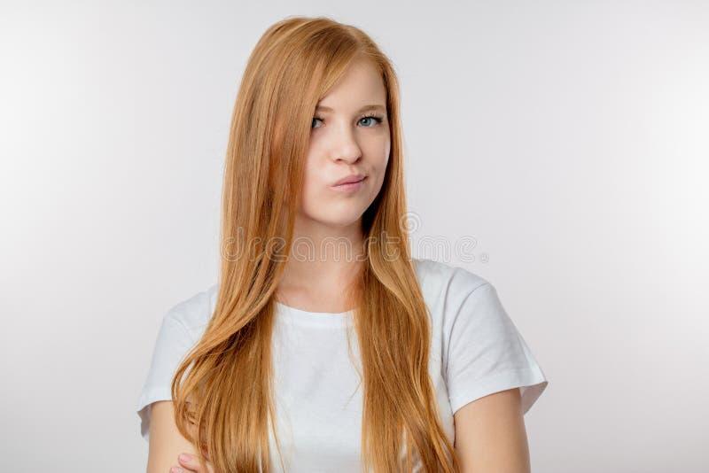 Den härliga redheaded flickan rynkar pannan, som hon ogillar med något royaltyfri foto