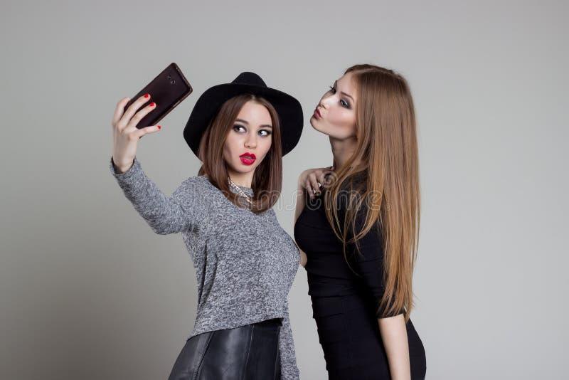 Den härliga roliga stygga flickvännen avlöser sig på telefonen som har gyckel som omkring bedrar i studion fotografering för bildbyråer