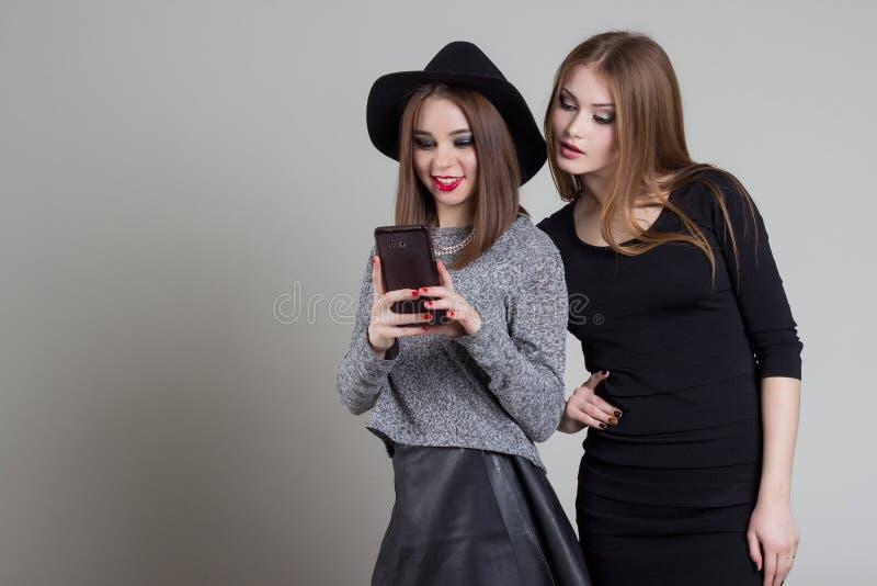 Den härliga roliga stygga flickvännen avlöser sig på telefonen som har gyckel som omkring bedrar i studion royaltyfria foton