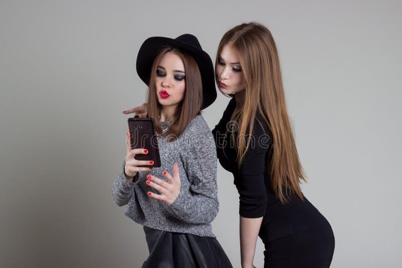 Den härliga roliga stygga flickvännen avlöser sig på telefonen som har gyckel som omkring bedrar i studion royaltyfri bild