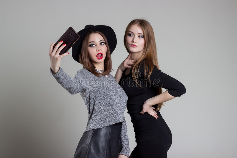 Den härliga roliga stygga flickvännen avlöser sig på telefonen som har gyckel som omkring bedrar i studion royaltyfri fotografi