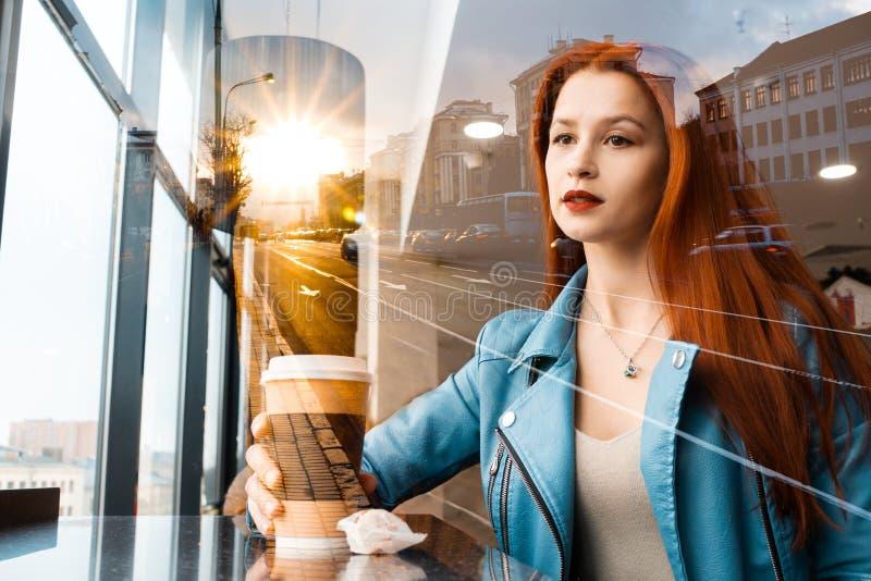 Den härliga romantiska flickan dricker kaffe i ett kafé rödhårig kvinna som sitter nära fönstret mot bakgrunden av staden växer royaltyfri bild
