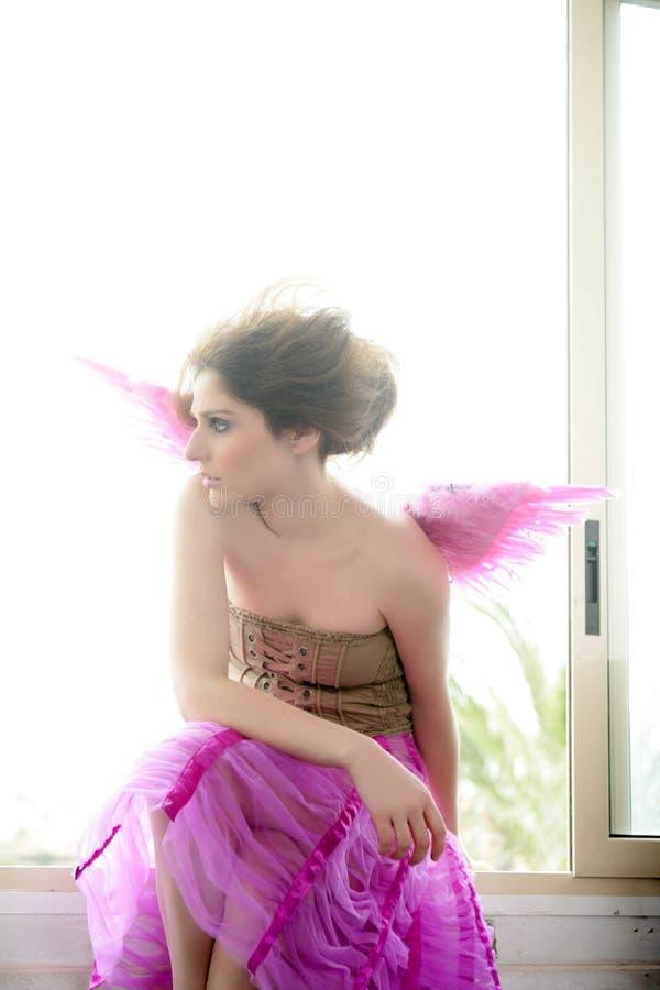 den härliga rosa redheaden wings kvinnan royaltyfri foto