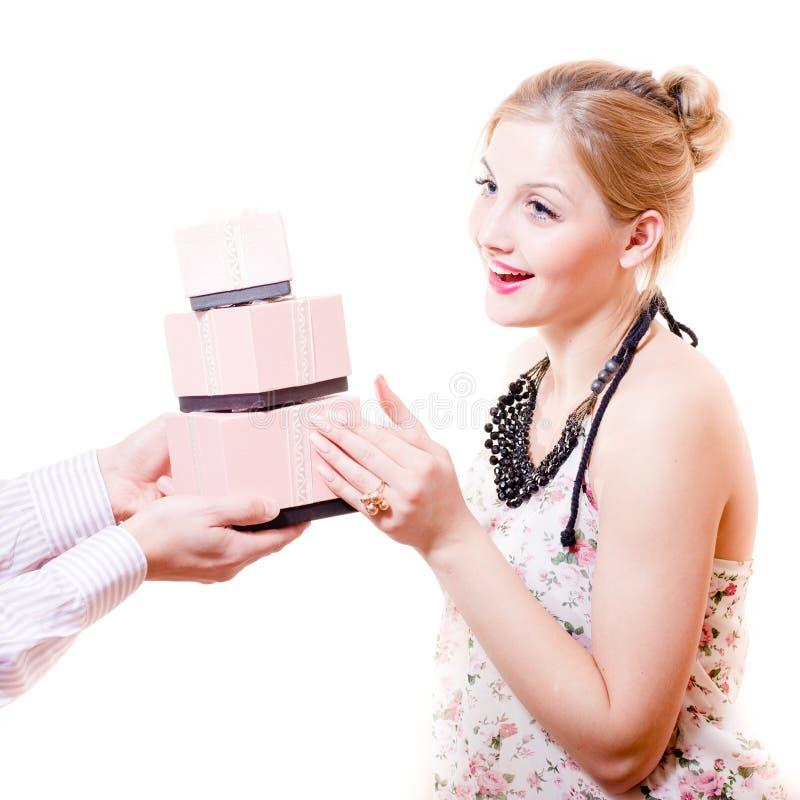 Den härliga söta, ärliga försiktiga blonda unga kvinnan mottog underbara gåvor i rosa askar från mans händer & lyckliga le arkivfoton