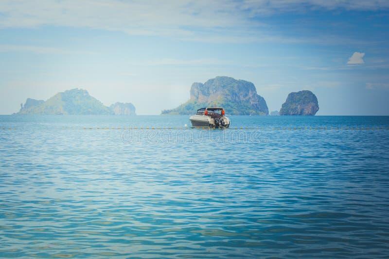 Den härliga seascapesikten av det ensamma hastighetsfartyget som svävar på havet med ön och blå himmel i bakgrunden på Railay, sä royaltyfri bild