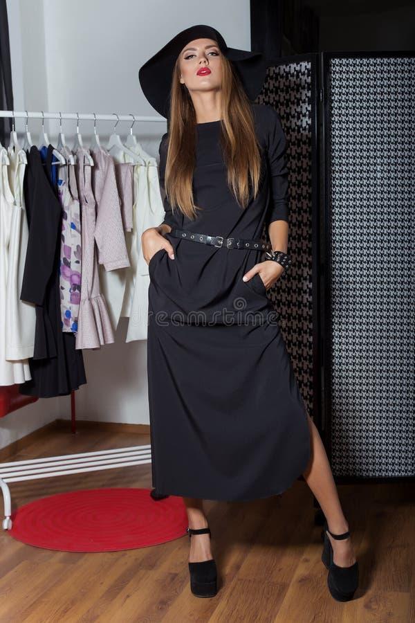 Den härliga sexiga attraktiva flickan i en svart hatt med röd läppstift i modefotografi i en svart klänning med en ljus afton gör arkivfoton