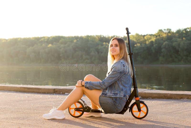 Den härliga sexiga blonda kvinnan i grov bomullstvillkläder sitter på hennes sparkcykel och ler på kameran arkivbild
