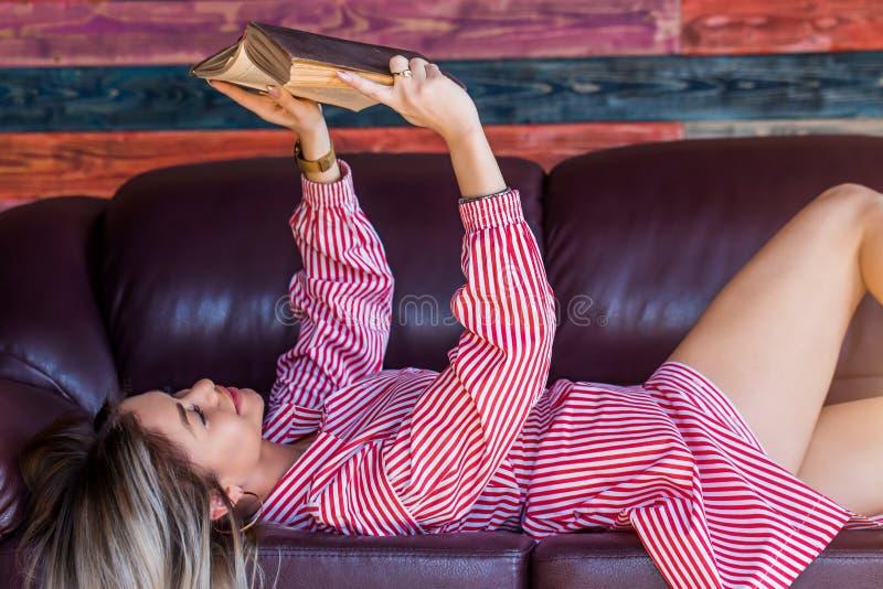 Den härliga sexiga blondinen tycker om helgen som läser en bok på soffan och le arkivbilder