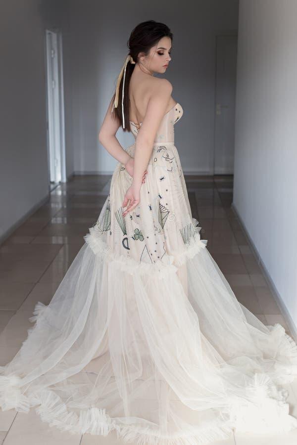Den härliga sexiga brunettflickan i elegant klänning med det långa drevet med lavendel blommar royaltyfri foto