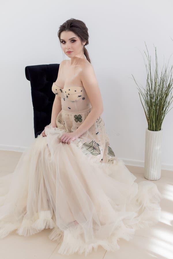 Den härliga sexiga brunettflickan i elegant klänning med det långa drevet med lavendel blommar royaltyfria bilder