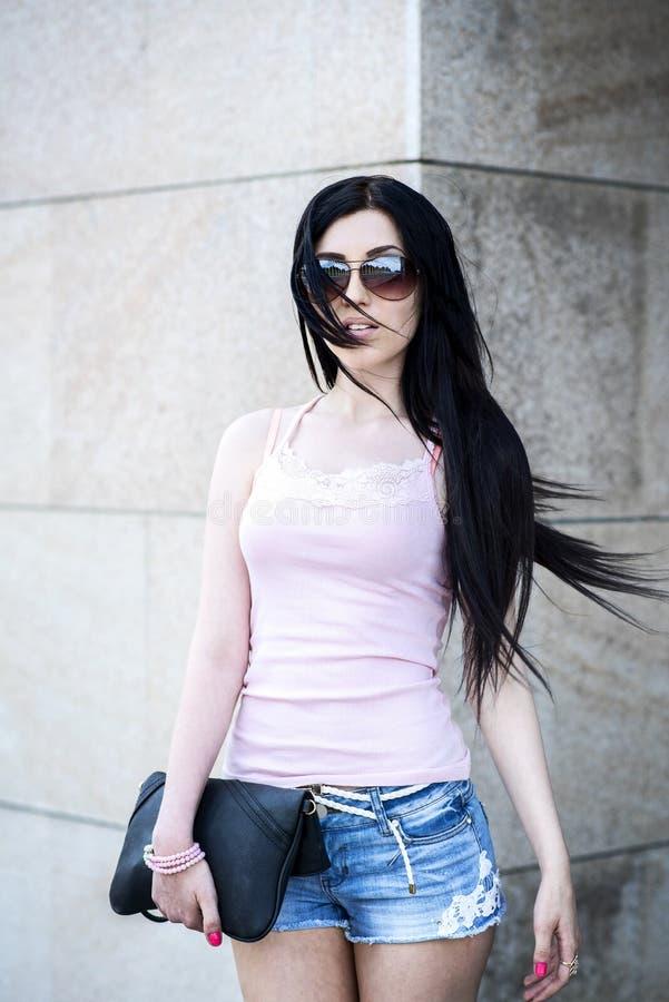 Den härliga sexiga brunettflickan som poserar i gatakortslutningen, kortsluter royaltyfri bild