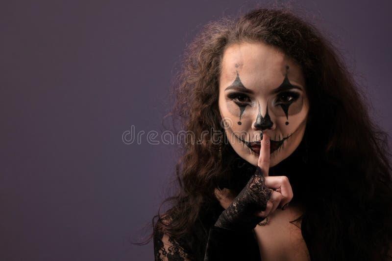 Den härliga sexiga flickan med halloween makeup satte ett finger till hennes kanter Dräktparti för alla helgon Begreppet av tystn royaltyfri bild