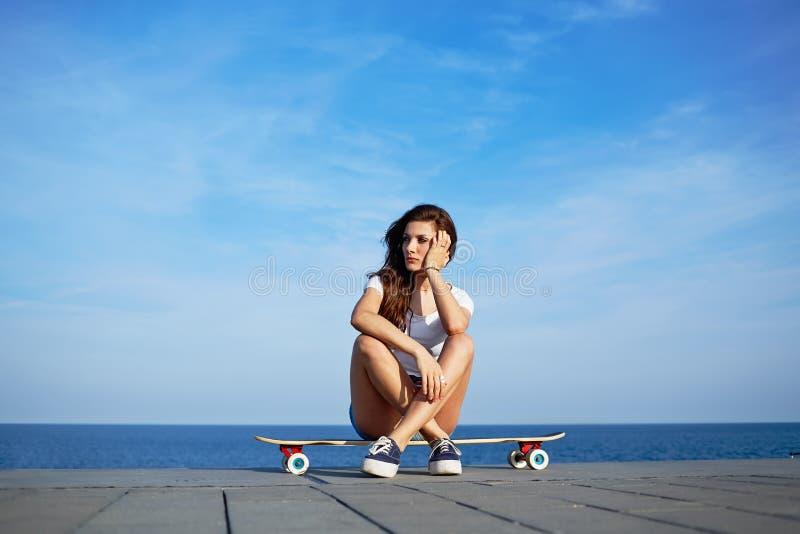 Den härliga sexiga flickan sitter på longboard med den fantastiska horisonten av havet på bakgrund royaltyfri foto