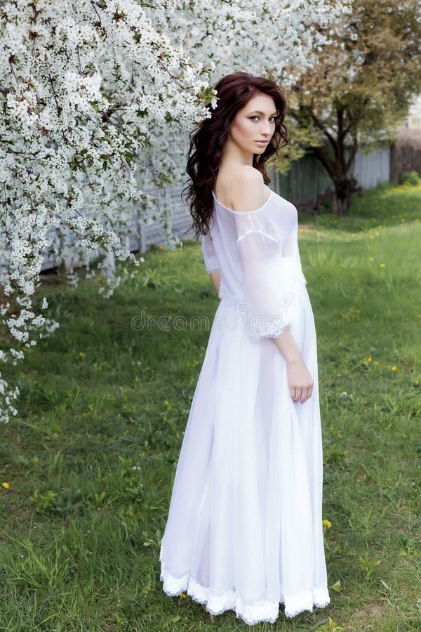 Den härliga sexiga gulliga försiktiga flickan går i en ljus vit klänning på en blomstra trädgård av den ljusa sommardagen royaltyfri bild