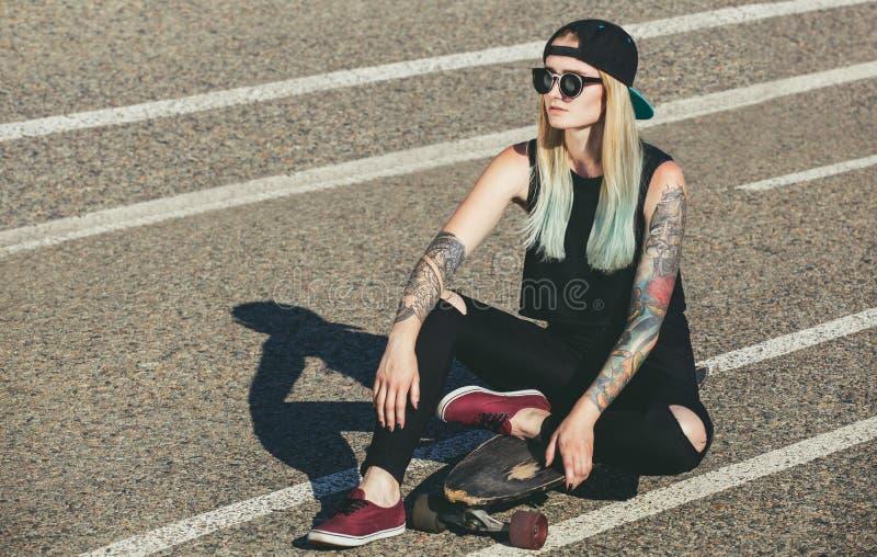 Den härliga sexiga hipsterblondinen med blått hår i tatuering sitter på en longboard med exponeringsglas och ett lock på asfalten arkivbilder