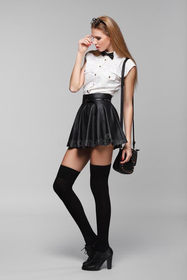 Den härliga sexiga kvinnan är i modestil i svart mini- kjol fashion flickan arkivbild